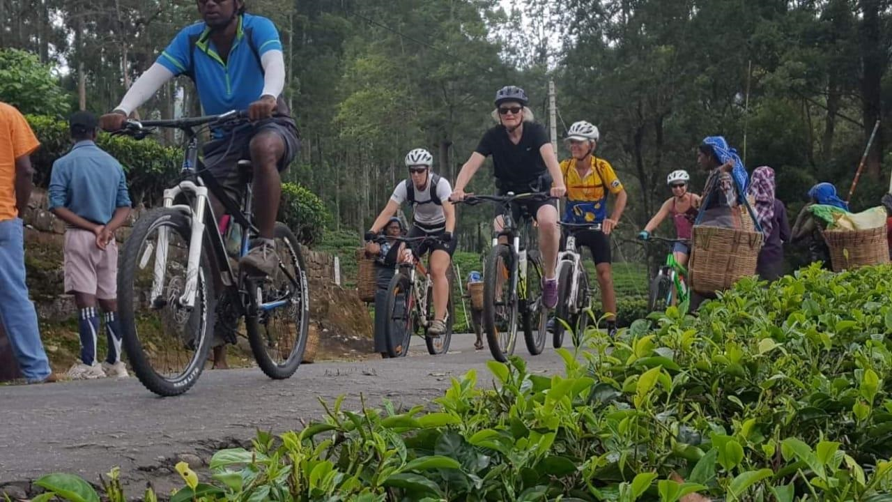 Group of tourists on bikes on a road with Sri Lankans at the side of the road
