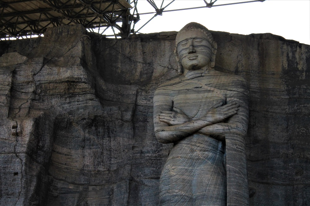 Statue of Buddha standing with crossed hands built in the rock