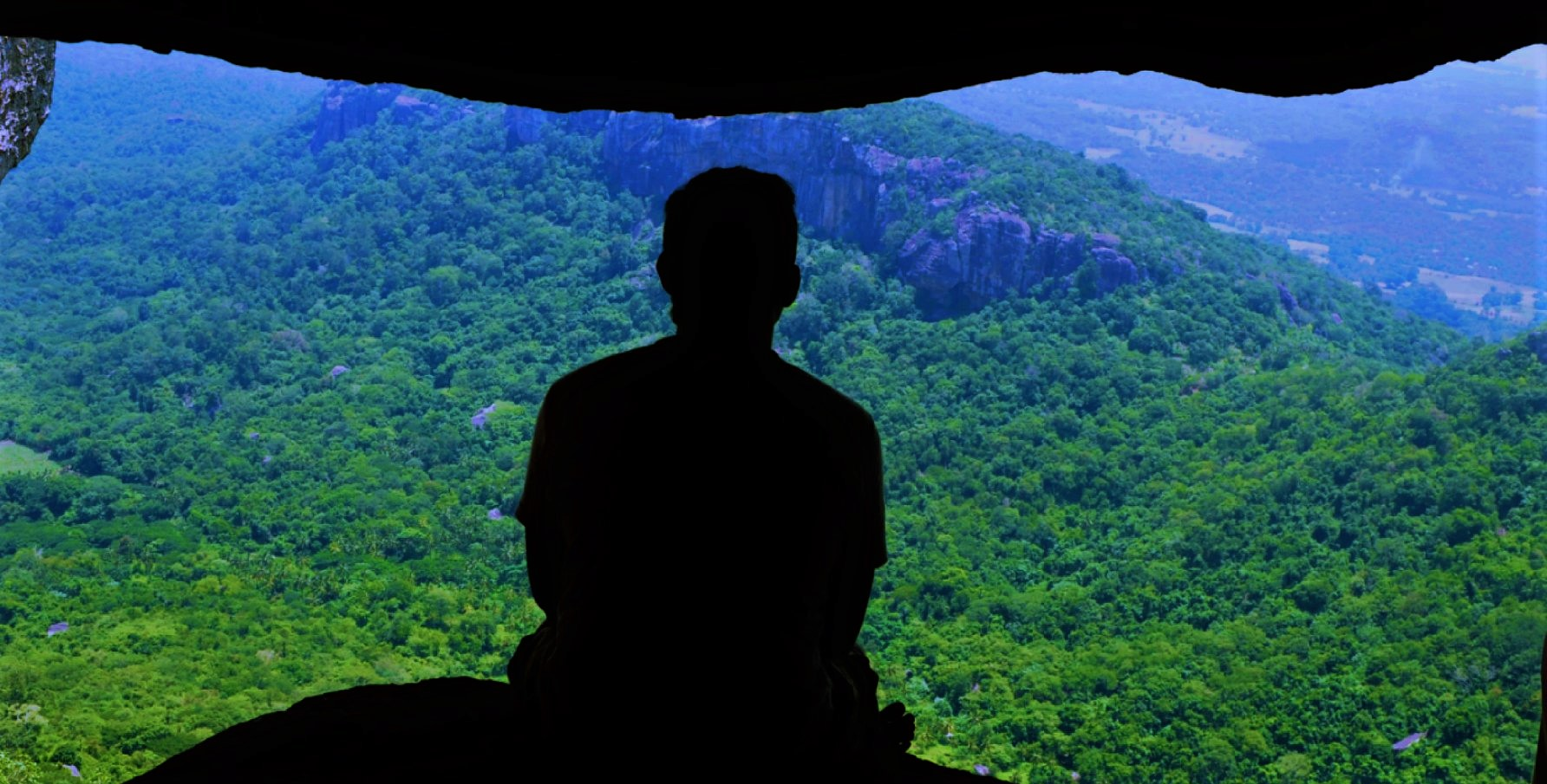 A man sitting in a cave looking at the landscape