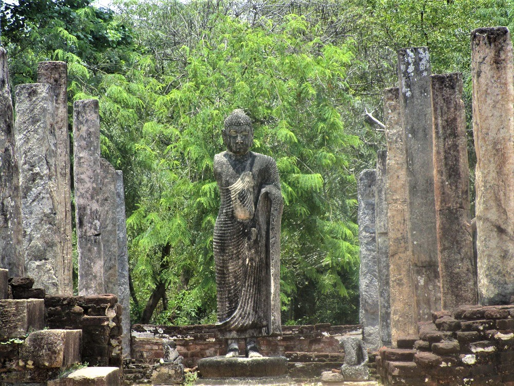 Stone buddha statue with one arm in front of a tree