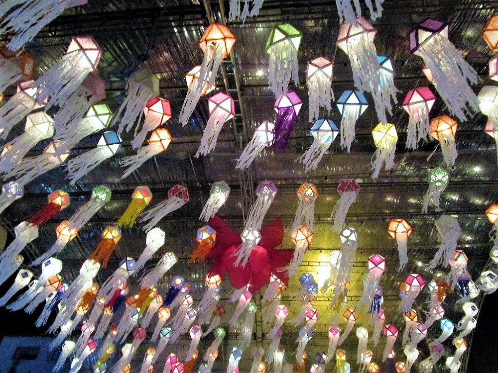 Many multicolored lanterns hanging from the ceiling